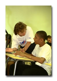 A paraprofessional works with a student at his desk