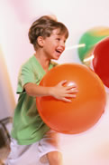 A picture of a boy running with a big orange, rubber ball.