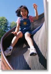 A girl slides down a playground slide.